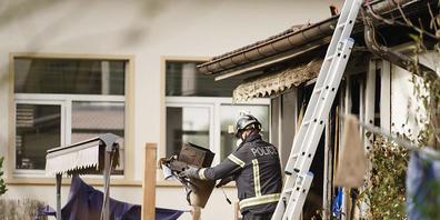 Ein Berner Kantonspolizist am Montag bei Aufräumarbeiten im vom Brand zerstörten Wohnhaus.