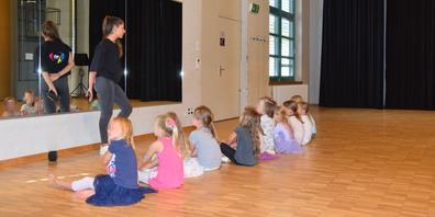 Aufmerksame Kinderaugen: Yara Auf der Mauer erklärt der Kindergruppe, was sie in der kommenden Tanzstunde machen werden.