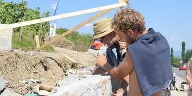 Baustellenleiter Felix Riegger und ein Zivildienstpflichtiger arbeiten gemeinsam an der Trockenmauer.