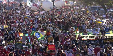 Demonstranten halten ein Banner hoch. Tausende Brasilianer sind gegen die Corona-Politik der Regierung von Bolsonaro auf die Straße gegangen. Foto: Eraldo Peres/AP/dpa