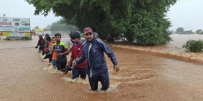 Mitarbeiter der National Disaster Response Force waten durch die Fluten. Der heftige Monsunregen hat mindestens 100 Menschen in Indien das Leben gekostet. Auch die Philippinen sind von den schweren Niederschlägen betroffen. Foto: -/AP/dpa