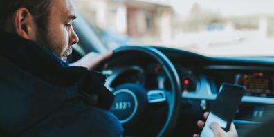 Viele machen es, doch es ist verboten und gefährlich: Handy checken beim Fahren.