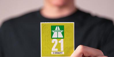 """Die Autobahnvignette 2021 hat die Grundfarbe """"grün metallic"""". Die Jahreszahl auf der Vorderseite ist weiss."""