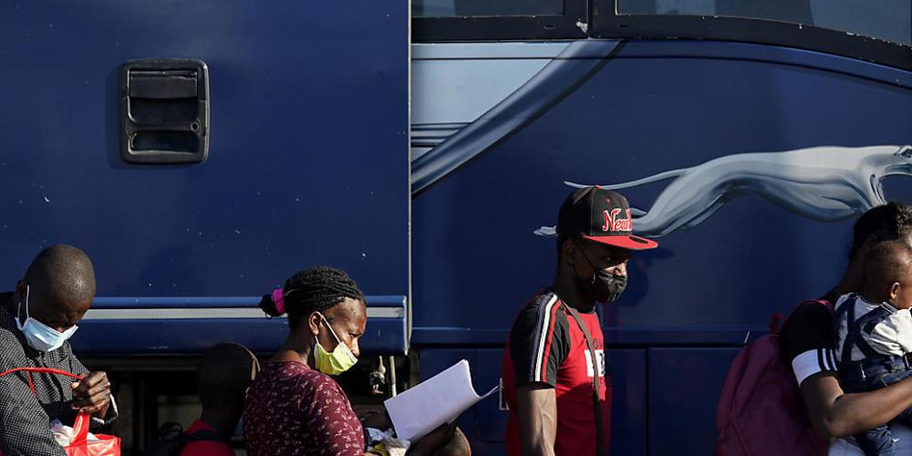 Migranten bereiten sich darauf vor, einen Bus zu besteigen, nachdem sie in einem behelfsmäßigen Lager nahe der Internationalen Brücke in Del Rio abgefertigt und entlassen wurden. Die USA wollen angesichts Tausender Migranten in der US-Grenzstadt D...