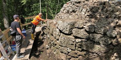 Denkmalpfleger (Lukas Wallimann) und Archäologe (Christian Bader) beurteilen den Zustand der vom Bewuchs befreiten Burgmauer.