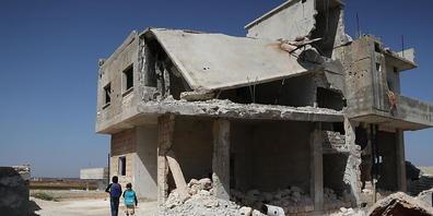 Kinder laufen an einem zerstörten Haus in Idlib vorbei, nachdem sie ihre Schule zu Beginn des Schuljahres verlassen haben. Foto: Anas Alkharboutli/dpa