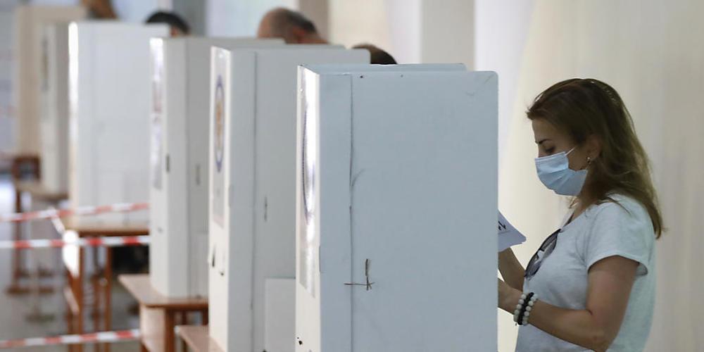 Menschen lesen während der Parlamentswahl in einem Wahllokal ihre Stimmzettel. Sieben Monate nach dem Krieg um die Konfliktregion Berg-Karabach wählt die krisengeschüttelte Südkaukasusrepublik Armenien ein neues Parlament. Foto: Sergei Grits/AP/dp...