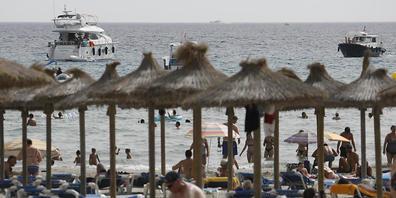Gäste liegen am Strand von Paguera auf Mallorca. Nach der angekündigten Hochstufung Spaniens zum Corona-Hochinzidenzgebiet gibt es zunächst keine Hinweise, dass viele Menschen ihren Urlaub vorzeitig abbrechen oder gebuchte Aufenthalte stornieren w...