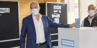 Enrico Michetti (l), Mitglied der rechtspopulistischen Partei «Fratelli d'Italia», wirft seinen Stimmzettel in die Urne. Foto: Mauro Scrobogna/LaPresse/AP/dpa