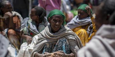 """ARCHIV - Eine äthiopische Frau schaufelt Weizenkörner auf, nachdem diese von der """"Relief Society of Tigray"""" im Norden Äthiopiens verteilt wurden. (Archivbild) Foto: Ben Curtis/AP/dpa"""
