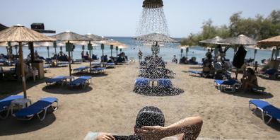 Eine Frau duscht an einem Strand des Dorfes Lagonissi, einige Kilometer südwestlich von Athen. Eine der schwersten Hitzewellen seit den 1980er Jahren ist über Südosteuropa hereingebrochen. In Teilen Griechenlands steigen die Temperaturen auf über ...