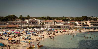 Urlauber kühlen sich am Strand Punta Prima auf Menorca ab. Die Corona-Zahlen sind in großen Teilen Spaniens rapide angestiegen. Deshalb stuft die deutsche Regierung laut Angaben des Robert Koch-Instituts Spanien von Dienstag an als Corona-Hochinzi...