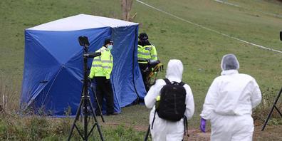 ARCHIV - Zwei Gerichtsmediziner gehen zu einem Zelt am Tatort auf dem Bugs Bottom Feld. Fünf Jugendliche sollen hier am 03.01.2021 einen 13-jährigen Jungen erstochen haben. In England hat ein Gericht zwei 14-Jährige wegen Mordes schuldig gesproche...