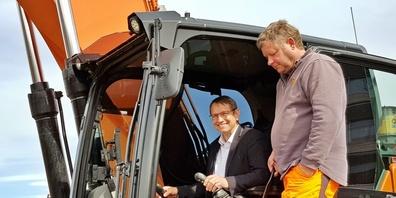 Gemeindepräsident Peter Hüppi steuert den Bagger nach kurzer Einweisung gekonnt.