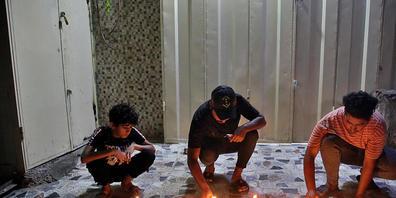 Menschen zünden Kerzen am Ort eines Bombenanschlags auf einem Markt in Bagdad an. Nach Angaben des irakischen Ministerpräsidenten ist die verantwortliche Terrorzelle gefasst worden. Foto: Khalid Mohammed/AP/dpa