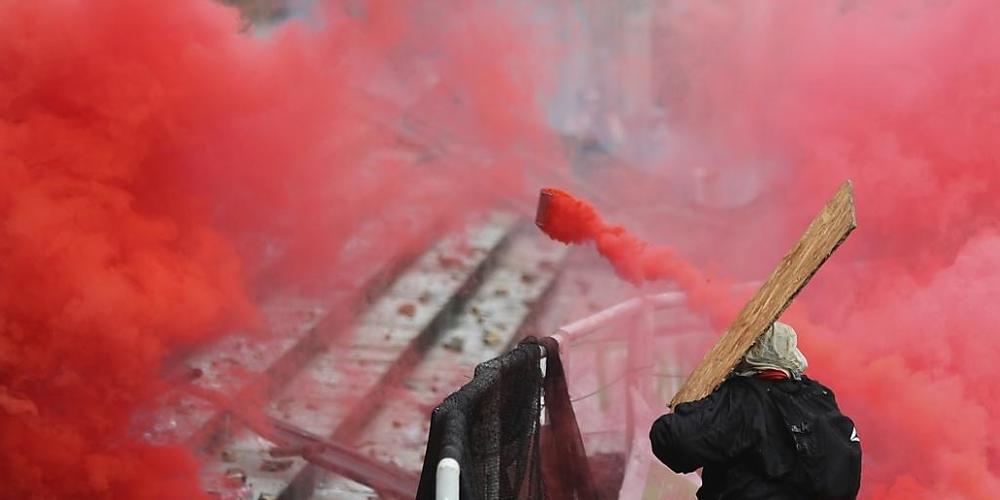Ein regierungskritischer Demonstrant wirft einen Tränengaskanister zurück. Foto: Fernando Vergara/AP/dpa