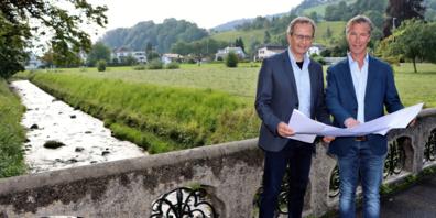 Der Rheinecker Stadtpräsident Urs Müller (links) und der Thaler Gemeindepräsident Felix Wüst (rechts) setzen sich für eine möglichst rasche Erhöhung der Hochwassersicherheit am Freibach ein. Auf der Wiese im Hintergrund soll ein Geschiebesammler entstehen