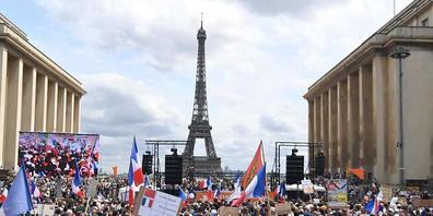 Demonstranten nehmen in Paris an einem Protest gegen die verschärften Corona-Regeln teil. Foto: Alain Jocard/AFP/dpa