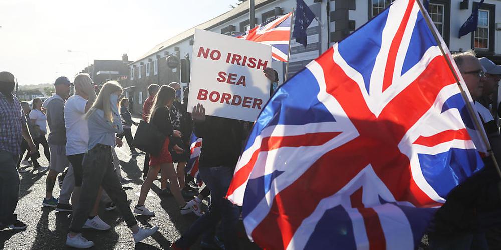 ARCHIV - Demonstranten halten britische Fahnen und ein Schild mit der Aufschrift «No Irish Sea Border» («Keine irische See-Grenze») bei einem Protest protestantischer Loyalisten gegen das sogenannte Nordirland-Protokoll. Foto: Brian Lawless/PA Wir...