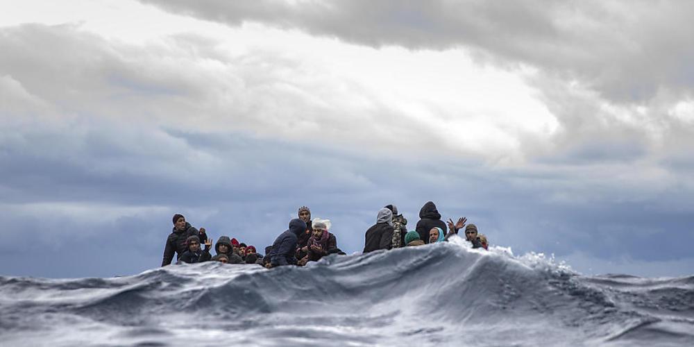 ARCHIV - Männer sitzen in einem überfüllten Holzboot im Mittelmeer vor der Küste von Libyen (Archivbild). Foto: Santi Palacios/AP/dpa