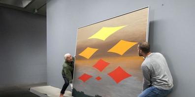 """Zwei Mitarbeitende bringen das Werk """"Neue Sterne"""" von Meret Oppenheim in die Ausstellungsräume des Kunstmuseums Bern."""