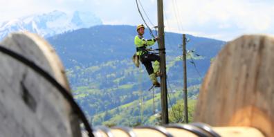 In luftiger Höhe wird das Freileitungsrohr für die Glasfasern an die bestehenden Masten angebracht.