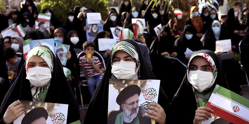 Unterstützerinnen des Präsidentschaftskandidaten Ebrahim Raisi halten während einer Demonstration für ihn Fotos von ihm. Foto: Ebrahim Noroozi/AP/dpa