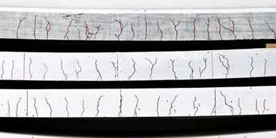 Ramponierte Betonplatten in verschiedenen Stärken. Von unten nach oben: unbehandelt, mit kohlefaserverstärktem Kunststoff versehen, zusätzlich gerillt, gerillt und vorgespannt (Pressebild).
