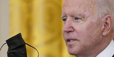 Joe Biden, Präsident der USA, hält seinen Mund-Nasen-Schutz während er im East Room des Weißen Hauses in Washington über die Impfvorschriften für Bundesbedienstete spricht. Foto: Susan Walsh/AP/dpa