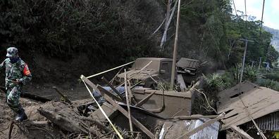 Ein indonesischer Soldat geht an Häusern vorbei, die durch einen von einem Erdbeben ausgelösten Erdrutsch in Bangli auf der Insel Bali beschädigt wurden. Foto: Dewa Raka/AP/dpa