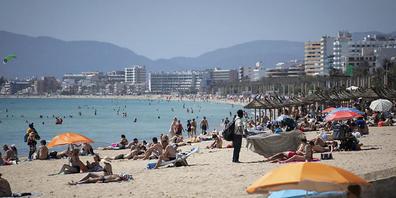 ARCHIV - Touristen genießen die Sonne an einem Strand auf der spanischen Insel Mallorca. Foto: Francisco Ubilla/AP/dpa