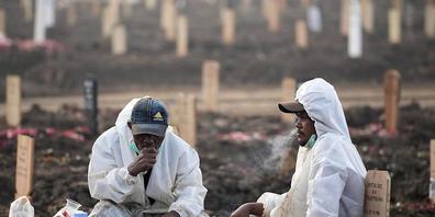 dpatopbilder - Mitarbeiter des Rorotan-Friedhof in Jakarta, welcher für Corona-Tote reserviert ist, tragen Schutzkleidung und sitzen während einer Pause zwischen den Gräbern. Foto: Dita Alangkara/AP/dpa
