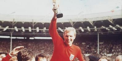 Die britische Fussballmannschaft bejubelt 1966 ihren Weltmeistertitel. Nachdem kürzlich bekannt wurde, dass Bobby Charlton (r) als fünftes Mitglied der damaligen Mannschaft an Demenz erkrankt ist, hat der britische Fussballverband Regeln zur Minim...