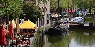 ARCHIV - Nur wenige Gäste sitzen bei sonnigem Wetter in den Außenbereichen der Cafés und Restaurants am Historischen Hafen in Rotterdam Foto: Soeren Stache/dpa-Zentralbild/dpa
