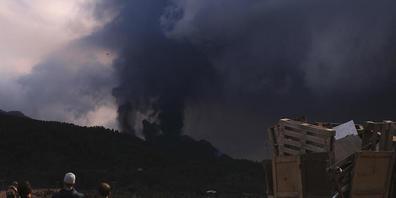 Menschen blicken von El Paso auf einen ausbrechenden Vulkan. Auf der Kanareninsel La Palma ist der Vulkanausbruch auch am Sonntag mit unverminderter Heftigkeit weitergegangen. Seit dem 19. September spuckt der Feuerberg in der Cumbre Vieja im Süde...