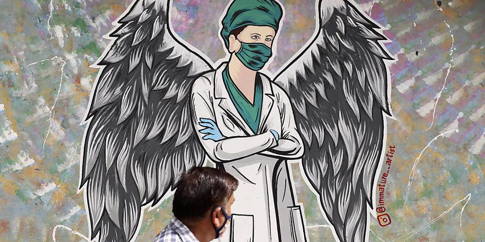 Ein Mann geht in Neu-Delhi  an einem Wandgemälde vorbei, das einen Mitarbeiter im Gesundheitswesen mit Flügeln zeigt. Indien hat heute einen neuen Tageshöchstwert an Todesfällen im Zusammenhang mit dem Coronavirus gemeldet. Foto: Amit Sharma/AP/dpa