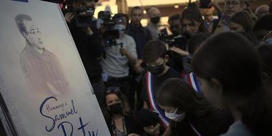 Eine Zeichnung zeigt den vor einem Jahr ermordeten Samuel Paty. Foto: Christophe Ena/AP/dpa