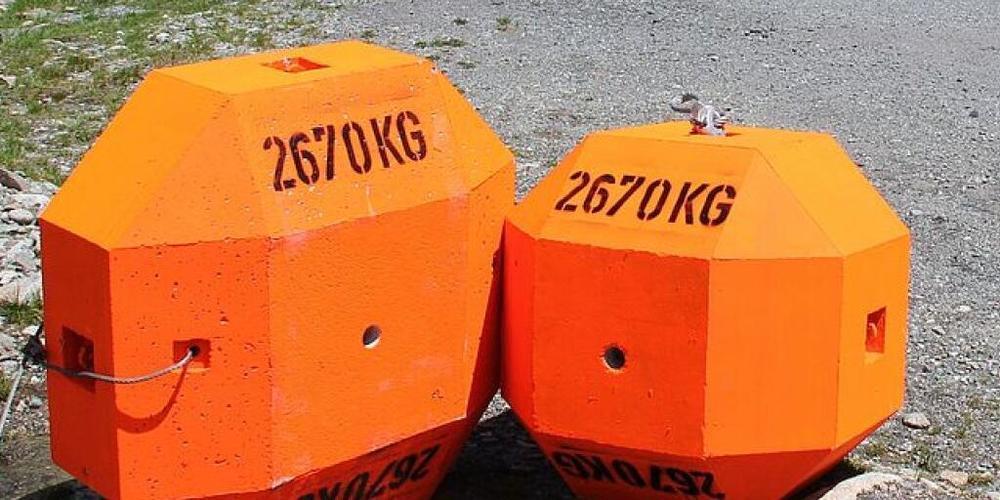 Das Risiko durch einen Steinschlag hängt mehr von der Form der fallenden Brockens ab als von dessen Masse. Im Bild zwei Kunststeine aus Beton, einer radähnlich und einer würfelförmig.