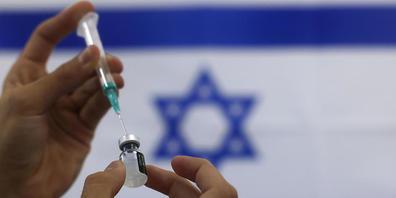 ARCHIV - Ein Sanitäter bereitet einen Impfstoff von Biontech/Pfizer vor. Israel will in Ausnahmefällen eine Impfung von Kindern gegen das Coronavirus erlauben, wenn diese stark gefährdet sind, im Falle einer Infektion schwer zu erkranken oder zu s...