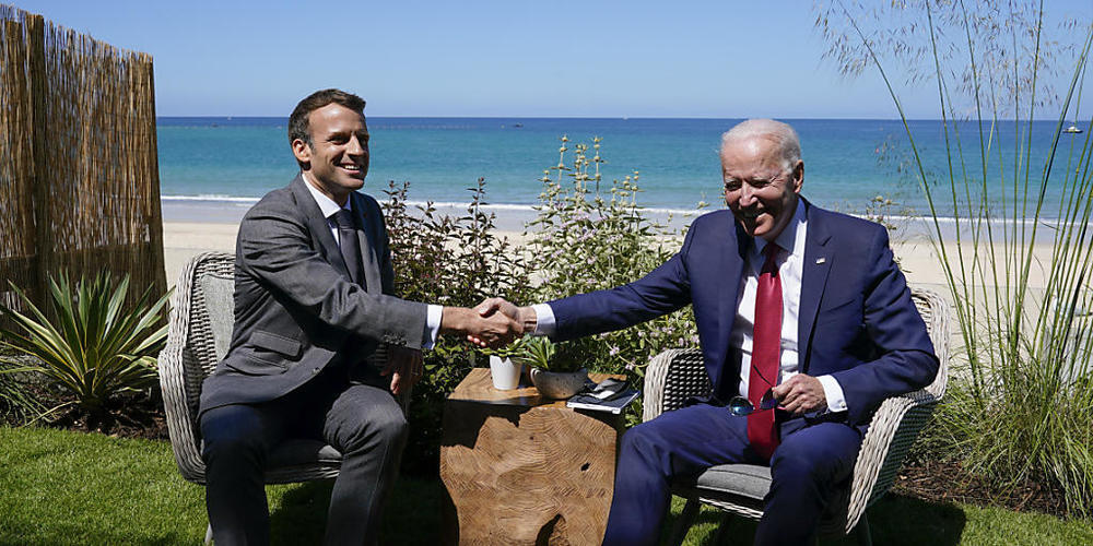 Joe Biden (r), Präsident der USA, und Emmanuel Macron, Präsident von Frankreich, schütteln sich die Hand bei einem gemeinsamen Treffen während des G7-Gipfels. Foto: Patrick Semansky/AP/dpa