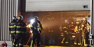 Feuerwehrleute löschen den brennenden Lastwagen in einer Werkstatt in Tägerwilen TG.