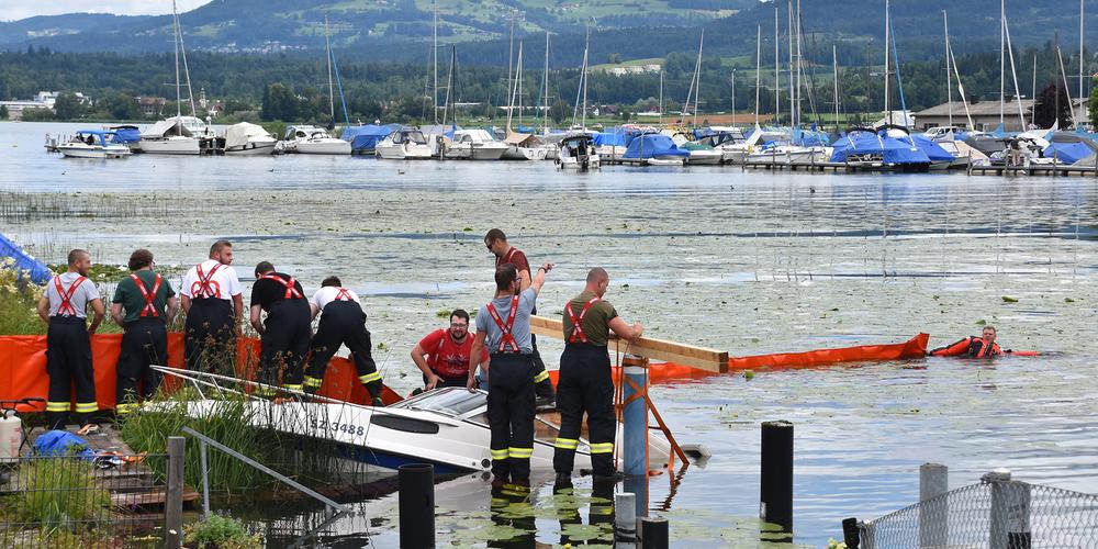 Mitglieder der Feuerwehr Wangen sichern das gesunkene Boot und errichten eine Ölsperre