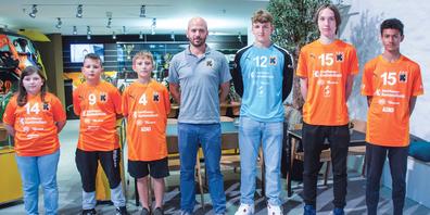 Die Juniorin und die Junioren der Kadetten Schaffhausen freuen sich mit Marco Lüthi über die neuen Tenüs.