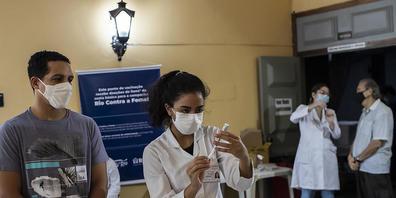 Eine Gesundheitsarbeiterin bereitet eine Spritze mit einem Corona-Impfstoff vor. Angesichts der verharmlosenden Politik der Regierung von Präsident Bolsonaro in Bezug auf die Pandemie sind tausende Brasilianer auf die Straße gegangen. Foto: Bruna ...