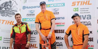 An der 17. Bündner Holzhauerei-Meisterschaft in Seewis holte sich  Arno Illien (Mitte) den Bündner Meistertitel vor Ralf Prinoth (l.) und  Nico Widmer (r.)