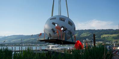 Das Globo uovo schwebt per Kran auf die Insel Ufnau.