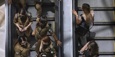 Menschen fahren ohne Mund-Nasen-Bedeckung und nahe nebeneinander auf einer Rolltreppe in einem Einkaufszentrum. Israel hatet 15.06.2021 nach der erfolgreichen Impfkampagne seine letzten Corona-Beschränkungen aufgehoben. Foto: Oded Balilty/AP/dpa