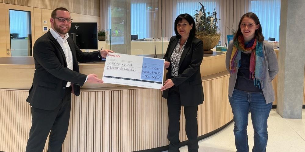 Bankleitungsmitglied Christian Hildebrand übergibt den symbolischen Check an Trudi Rutz, Präsidentin Bibliothek Nesslau und Debora Lindner, Bibliotheksleiterin