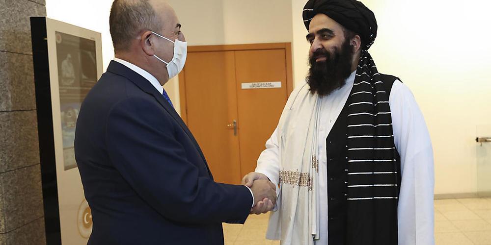 HANDOUT - Mevlüt Cavusoglu (l), Außenminister der Türkei, und Amir Khan Muttaqi, Außenminister von Afghanistan, geben sich während ihres Treffens die Hand. Erstmals seit der Machtübernahme in Afghanistan ist eine Delegation der Taliban zu Gespräch...