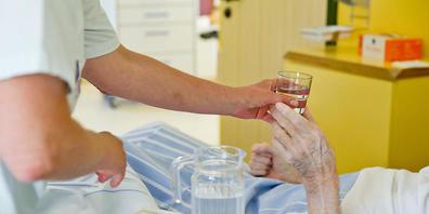 ARCHIV - Eine Krankenpflegerin reicht einem Patienten ein Glas Wasser. Durch den Brexit hat sich in Großbritannien der Pflegemangel deutlich verschärft. Vor allem bei der Betreuung von Behinderten fehle es an Personal, berichtete der «Observer» am...